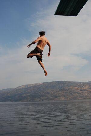 Man jumping from a jumping board into okanagan lake.