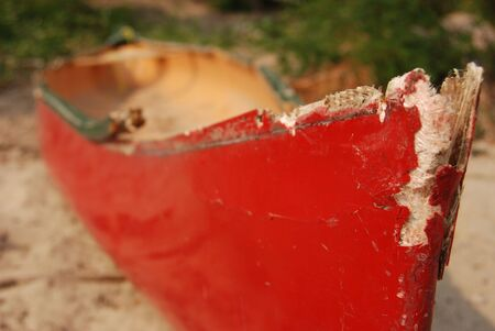 A old red broken boart lying on the beach