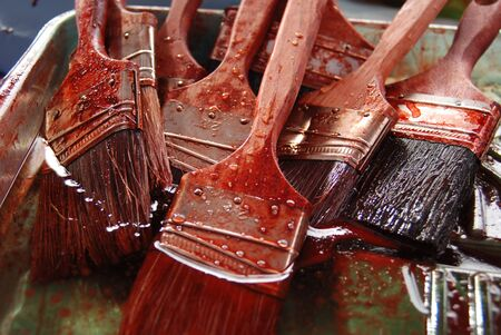 A couple of brushes soaked in red paint