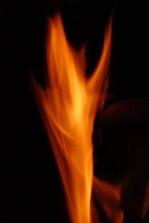 A beautiful flame over burning wood in a fireplace.  Stock Photo