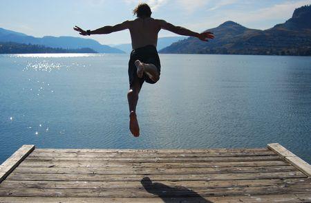 Man jumping from a pontoon into okanagan lake.