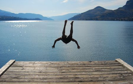 Man jumping from a pontoon into okanagan lake. photo