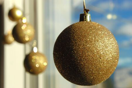 A golden ball hanging on a window Stock Photo