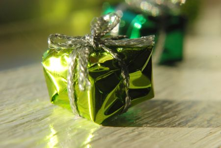 Three tiny decorative green and golden Christmas presents