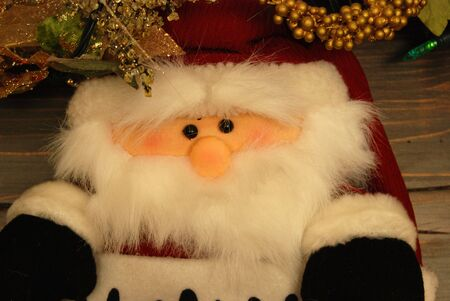 A decorative santa claus puppet hanging on a wood plank. Stockfoto