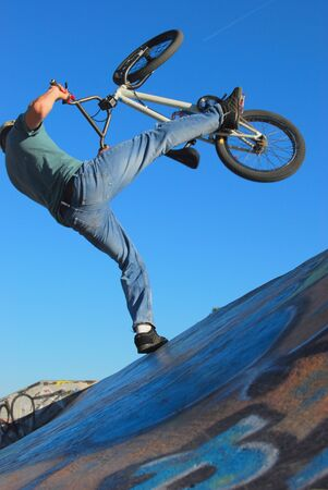 A man jumping high with his bmx bike in westbank skatepark.