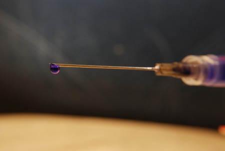 Close-up of a needle and syringe with blue drop of vaccination liquid.