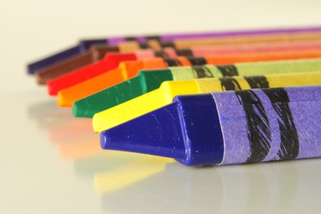 Crayons in different colors lying on a shiny desk Stock Photo