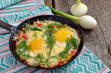 Fried eggs with greens, vegetables and cheese on a frying pan  photo