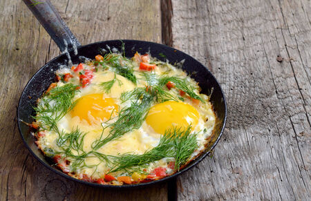 Fried eggs with greens, vegetables and cheese on a frying pan. photo