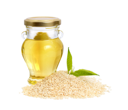 Sesame oil with seeds. Isolated on white background. Stock Photo