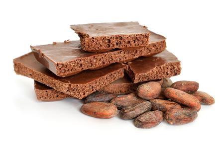 Melkluchtchocolade met cacaobonen voor het roosteren. Geïsoleerd op een witte achtergrond. Stockfoto