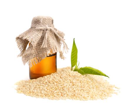 ajonjoli: El aceite de sésamo con semillas. Aislado en el fondo blanco.