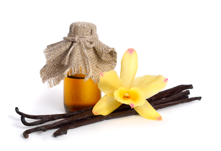 Vanilla essential oil in pharmaceutical bottle with pods and one yellow orchid. Isolated.