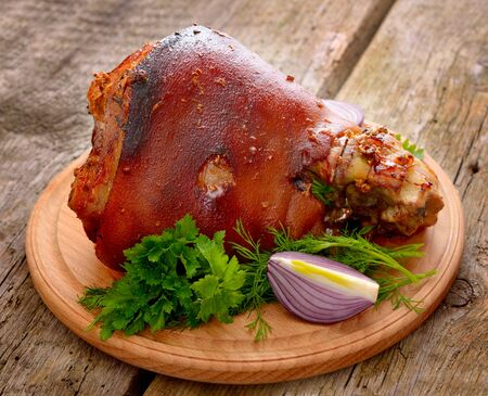 meat and alternatives: Baked Eisbein with wegetables on wooden board.
