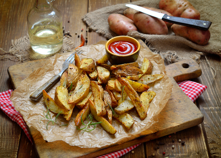 Potato wedges with a peel fries on parchment. Rural still life on old boards. Stock Photo