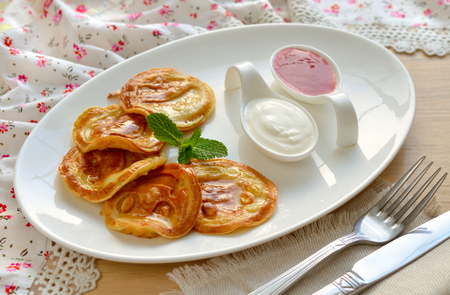 Pancakes with strawberry sauce and sour cream.