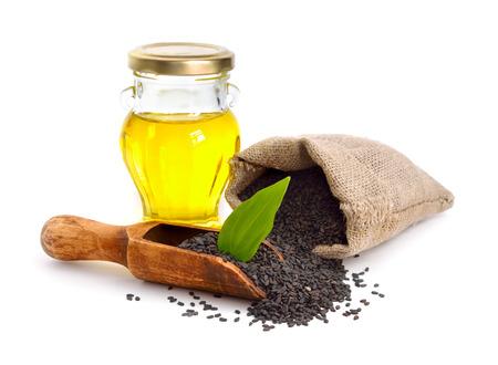 Schwarzer Sesam mit Öl. Isoliert auf weißem Hintergrund.