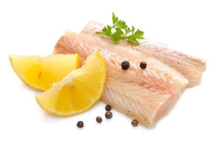 burbot: piezas de filete de pescado sin procesar de la merluza con lim�n. Aislado en el fondo blanco. Foto de archivo