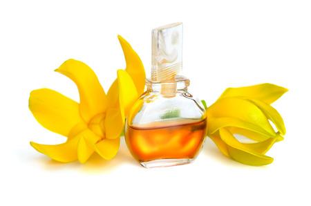 Ylang-ylang aceite esencial con flores. Aislado en el fondo blanco. Foto de archivo