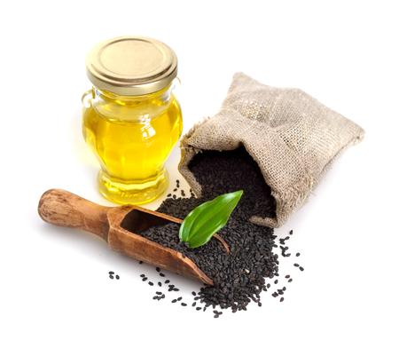 Schwarzer Sesam mit Öl. Isoliert auf weißem Hintergrund. Standard-Bild