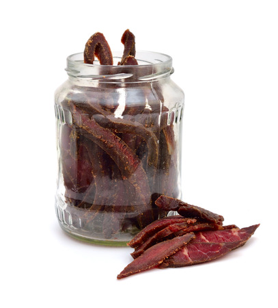 Beef Jerky in a glass jar isolated on white background.