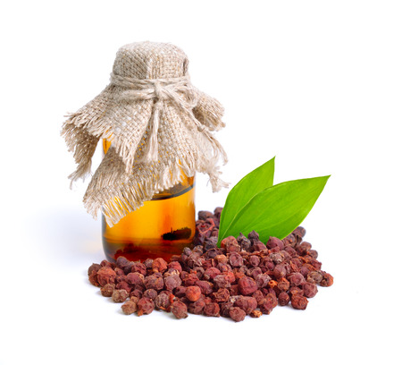 wei: Schisandra chinensis, magnolia-vine, Chinese magnolia-vine, schisandra, magnolia berry, five-flavor-fruit,  wu wei zi. Dried fruit with pharmaceutical bottle isolated.