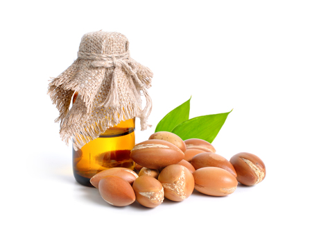 Argan seed  with pharmaceutical bottle. Isolated  on white background. Foto de archivo