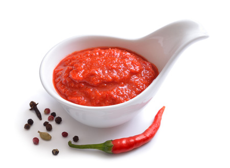 Red chili sauce in the sauce boat. With pepper. Isolated on white background. Stock Photo