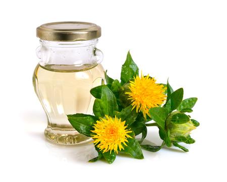 瓶に油とサフラワー植物。白い背景上に分離。