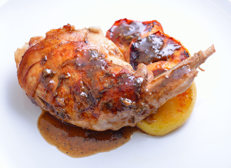 Sous Vide rabbit leg with sous and grilled apple on white plate. Stock Photo