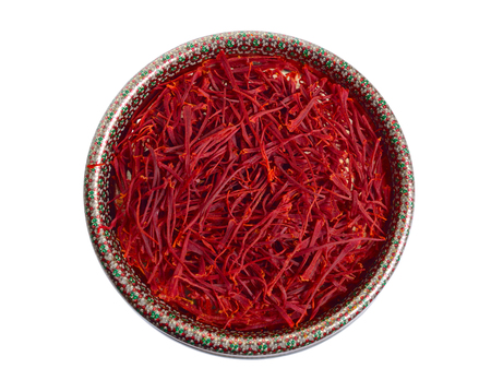 Delicati fili di zafferano, strappati dai fiori di croco ed essiccati. Nella scatola etnica. Isolato su sfondo bianco.