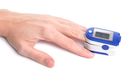 Pulse oximeter with hand of patient isolated on white background