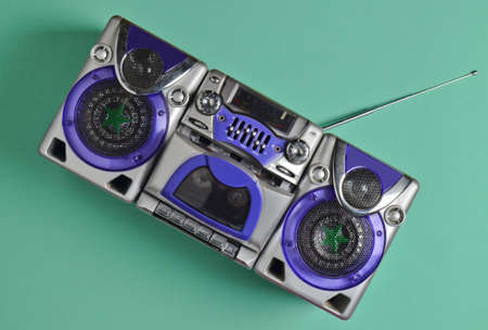 Retro tape recorder on mint-colored pastel background. Technology 80s. Top view.