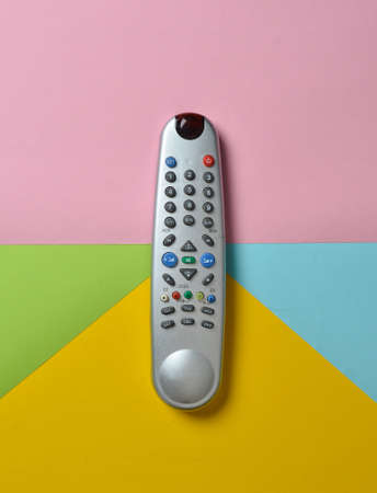 TV remote control on a multi-colored pastel background