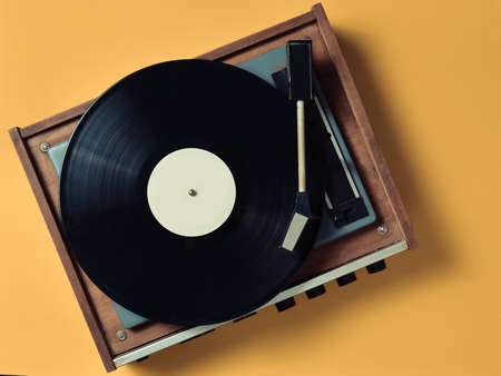 Vintage vinyl turntable with vinyl plate on a yellow pastel background. Entertainment 70s. Listen to music. Top view. Фото со стока