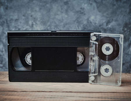 Audio and video cassette close-up on a wooden shelf against a gray concrete wall. Retro technology for listening to music and watching videos. Stock Photo