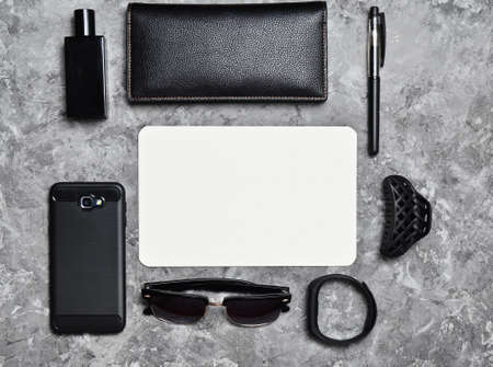 Working space. Accessories for a business woman on a concrete table. Space for text. Wallet, sheet of paper, perfume, sunglasses, smart watch, smartphone, pen. Trend of minimalism. Top view.