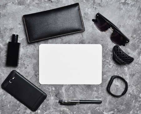 Working space. Accessories for a business woman on a concrete table. Space for text. Wallet, sheet of paper, perfume, sunglasses, smart watch, smartphone, pen. Trend of minimalism. Top view. Stock Photo