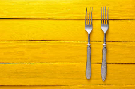 Two antique forks on a wooden table in yellow. Top view. Copy space.