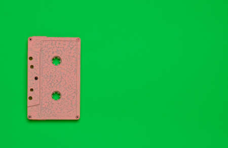 Retro audio cassette on a green bright colored background. Old school technology 80s. Copy space. Top view.