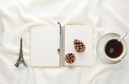 Morning inspiration, cup of tea, notebook with a pen, pine cone, souvenir on a white bed sheet. Breakfast on the bed. The concept of dreams and the desire to travel. Top view.