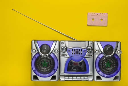 Old school retro tape recorder and audio cassette on a green background. Obsolete technologies. Trend of minimalism. Top view. Copy space.