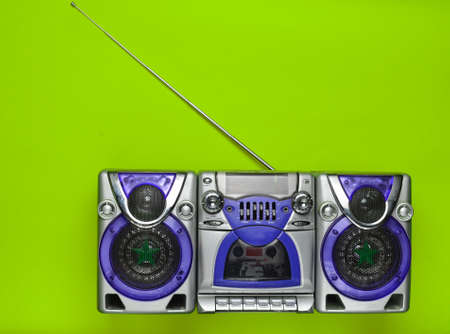 Old school retro tape recorder on a green background. Obsolete technologies. Trend of minimalism. Top view. Copy space.