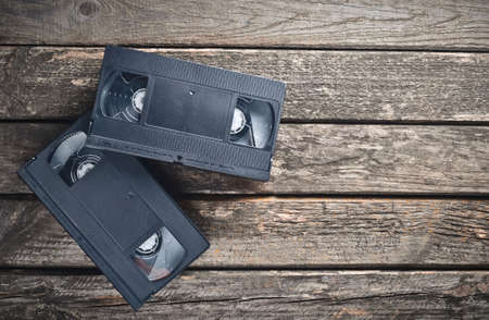 Two plastic video cassettes from the 80s on a rustic wooden table. Top view. Stock Photo