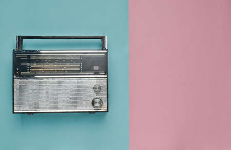 Retro radio receiver on a pink blue pastel background. Media technology 60s. Top view.