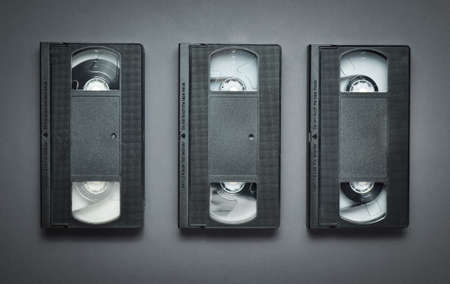 Three video cassettes on a gray background. Retro technology from the 80s. Top view.