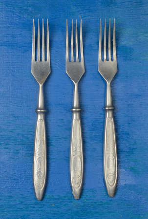 A set of forks on a blue wooden surface. Top view.