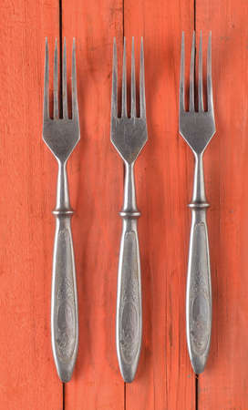A set of forks on an orange wooden surface. Top view.