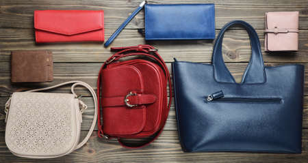 Many women's bags and purses on a wooden background. Top view.